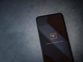Adobe Illustrator desenha a tela de início do aplicativo com logotipo na tela de um smartphone móvel preto em um fundo de pedra de mármore escuro foto