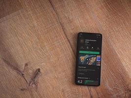 Adobe Illustrator desenha a página da app play store na tela de um smartphone móvel preto em um fundo de madeira foto