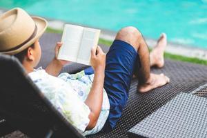 homem lendo livro perto da piscina. relaxe o conceito. foto
