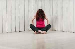 garota com blusa esporte rosa, sentada de pernas cruzadas no chão, luz de fundo foto