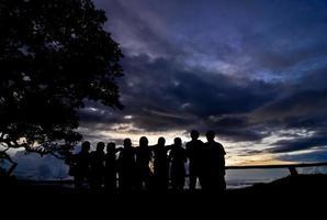 silhueta do fotógrafo tirando foto da paisagem durante o nascer do sol