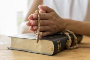 pessoa orando com o livro sagrado do rosário foto