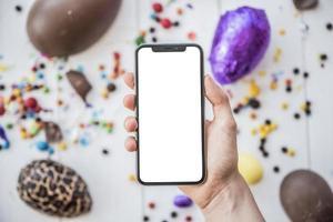 pessoa segurando um smartphone com ovos de páscoa de tela em branco foto