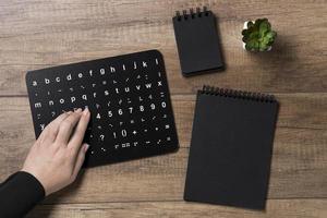 mão lendo quadro do alfabeto em braille foto