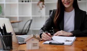 corretora imobiliária profissional fazendo um documento de contrato de aluguel em papel no escritório foto