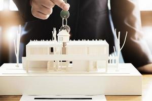 os corretores imobiliários concordam em comprar uma casa e dar as chaves aos clientes nos escritórios de suas agências. acordo de conceito. foto