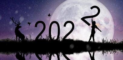 silhueta de mulheres segurando o número 2 na colina, enquanto comemorava 2022 anos no plano da Via Láctea. foto