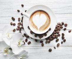uma xícara de café com padrão de coração em uma mesa foto