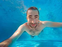 jovem bonito mergulhando debaixo d'água em uma piscina foto