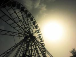 silhueta de uma roda gigante ao pôr do sol foto
