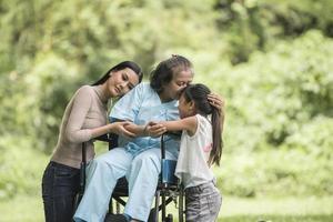 avó feliz em cadeira de rodas com a filha e o neto em um parque, vida feliz, tempo feliz. foto