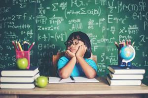 menina pensativa com livro perto de um conselho escolar foto