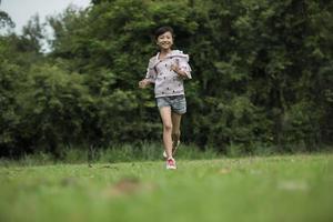 menina feliz e fofa correndo na grama do parque foto