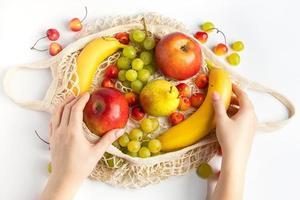mulher coloca frutas maduras em uma sacola de malha ecológica para fazer compras. mãos femininas seguram um saco de algodão com produtos agrícolas orgânicos. estilo de vida sustentável. foto