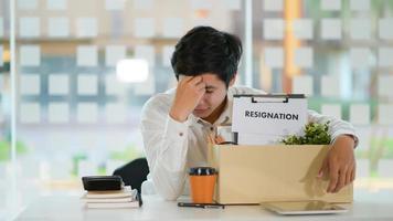 o conceito de demissão, funcionário do sexo masculino com uma caixa de armazenamento para o equipamento após a demissão, ele curvou o rosto estressado. foto