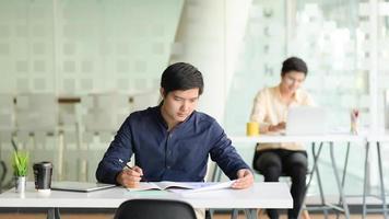 dois homens de negócios profissionais trabalham juntos em projetos em um escritório moderno. foto