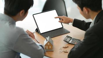 os corretores de seguros com tablet estão apresentando programas de seguros imobiliários para os clientes. foto
