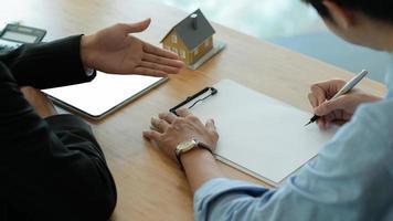 os agentes de seguros estão apresentando aos clientes a assinatura de contratos de seguro imobiliário. foto