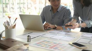 uma equipe de designers profissionais está trabalhando com smartphones e laptops para criar aplicativos. foto