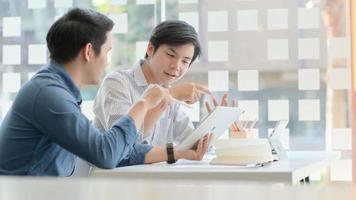 dois jovens profissionais de negócios estão discutindo seus projetos futuros com um confortável laptop sobre a mesa do escritório. foto
