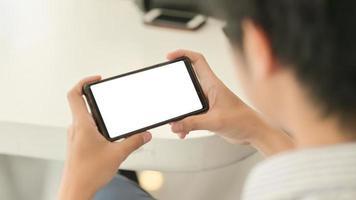 foto recortada do empresário segurando a tela em branco smartphone horizontal sentar-se relaxado na cadeira em um escritório confortável.