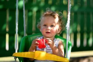 lindo menino com balanço de criança posando fotógrafo foto