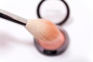 close-up do pincel de maquiagem e da caixa de blush isolado no fundo branco foto