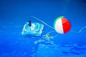 bola de praia colorida flutuando na piscina e ao lado dele embaixo d'água um robô de limpeza foto