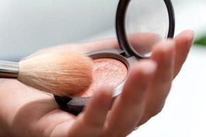 close-up das mãos de uma mulher segurando um pincel de maquiagem e uma caixa de blush foto