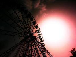 silhueta de uma roda gigante em um fundo de céu vermelho foto