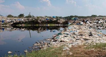 água poluída e montanha grande pilha de lixo e poluição, pilha de fedor e resíduos tóxicos, esses resíduos vêm de áreas urbanas e industriais não podem se livrar de foto