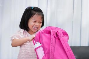 garotas asiáticas estão se divertindo fazendo as malas para a escola. alunos do jardim de infância com mochilas escolares rosa. foto