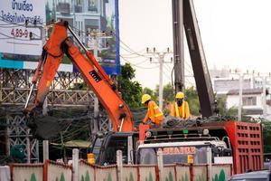 Bangkok, Tailândia, 09 de outubro de 2019 - dois capatazes estavam no caminhão, eles usavam capacetes amarelos, usavam camisas de manga comprida laranja duas escavadeiras estão trabalhando em grandes máquinas industriais segurança no trabalho foto