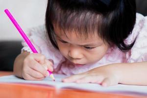 linda garota asiática está colorindo uma cor de madeira-de-rosa em um livro. criança olhou para o close up. conceito de postura sentada e problema com os olhos. foto