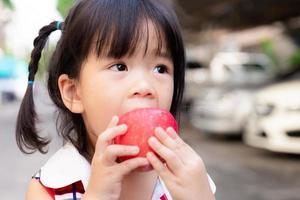 linda garota está usando a mão para segurar uma maçã e mordê-la com delicadeza. criança asiática come frutas vermelhas frescas. foco suave. criança de 3 anos e meio. foto