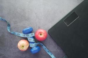 conceito de fitness com halteres, maçã e escala de peso no preto foto