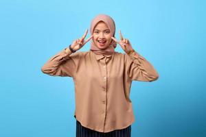 retrato de uma jovem asiática alegre fazendo sinal da paz com as mãos dos dedos sobre o fundo azul foto