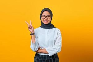 mulher asiática jovem e alegre mostrando o símbolo da paz em fundo amarelo foto
