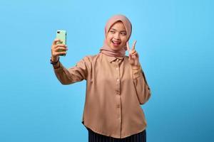 retrato de mulher asiática jovem alegre usando telefone celular, tirar selfie, fazer o símbolo da paz foto