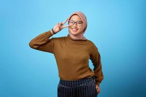 mulher asiática jovem e alegre mostrando o símbolo da paz sobre o olho no fundo azul foto