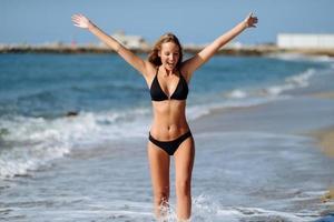 jovem loira com corpo bonito em trajes de banho em uma praia tropical com os braços abertos. foto