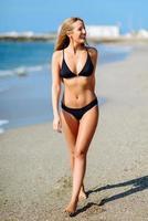 jovem loira com corpo bonito em trajes de banho em uma praia tropical. foto