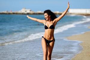 jovem mulher árabe com belo corpo em trajes de banho sorrindo em uma praia tropical. foto
