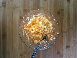 cenoura com repolho em uma tigela de vidro, vista de cima, salada para o almoço, fundo de madeira foto
