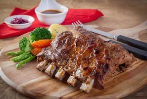 bife de porco cru na mesa de madeira foto