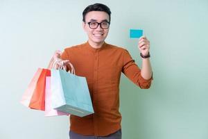jovem asiático segurando sacola de compras sobre fundo verde foto