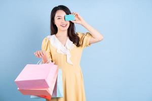 bela jovem asiática segurando uma sacola de compras sobre fundo azul foto