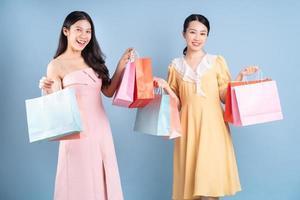 duas jovens mulheres asiáticas segurando uma sacola de compras sobre fundo azul foto