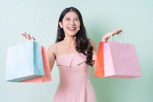 bela jovem asiática segurando uma sacola de compras sobre fundo verde foto