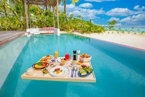 café da manhã na piscina, café da manhã flutuante em luxuoso resort tropical. mesa relaxante na água calma da piscina, saudável café da manhã fruta prato hotel resort piscina. casal tropical praia luxo estilo de vida foto